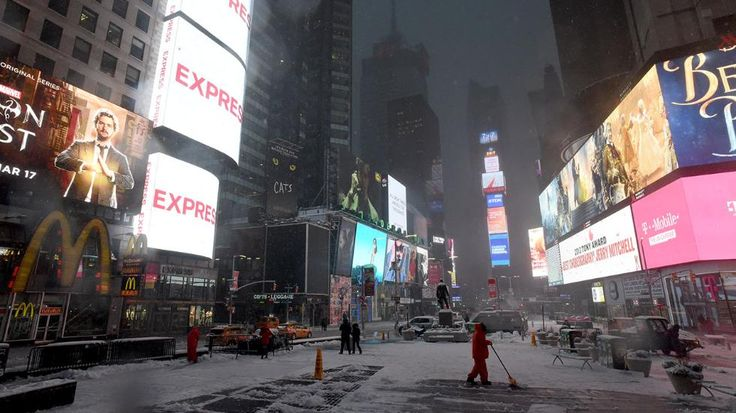 Workers clear the sidewalks from ice and snow in Times Square in New York on March 14, 2017. Winter Storm Stella dumped snow and sleet Tuesday across the northeastern United States where thousands of flights were canceled and schools closed, but appeared less severe than initially forecast. After daybreak the National Weather Service (NWS) revised down its predicted snow accumulation for the city of New York, saying that the storm had moved across the coast. (Eric Baradat/AFP/Getty Images)