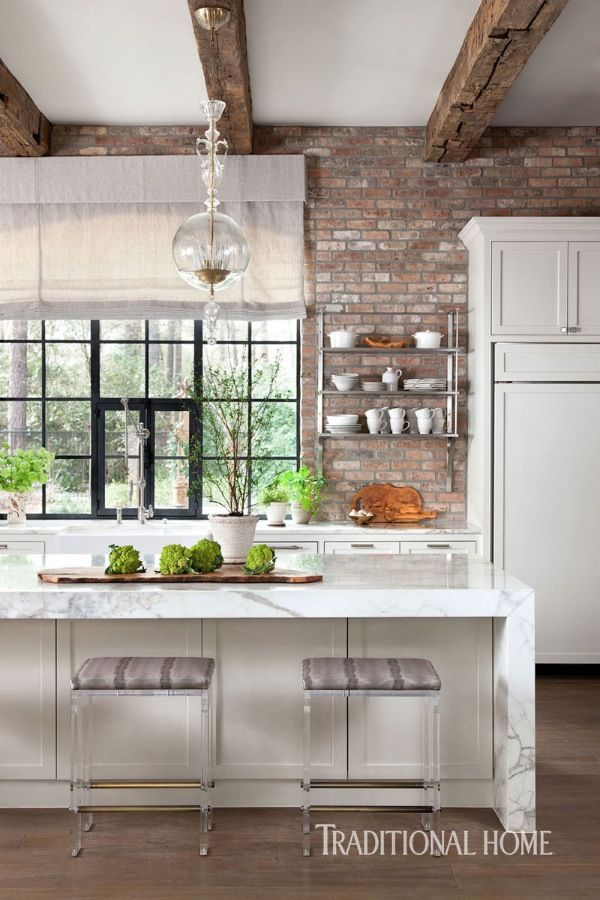 To add a rustic vintage feel, the window wall is clad with bricks in muted shades of red, a contrast to the smooth white marble. - Photo: Ryann Ford / Design: Julie Dodson