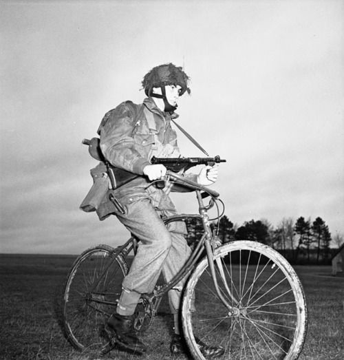 Private Tom J. Phelan of the 1st Canadian Parachute Battalion, 6th British Airborne Division, who was wounded on 16 June 1944 at Le Mesnil, rides his airborne folding bicycle at the battalion's reinforcement camp; England - 1944