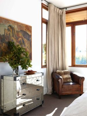 A Toss Woollaston canvas hangs in a guest bedroom; the reflective art deco chest and leather armchair are from Gary Mahon Gallery.