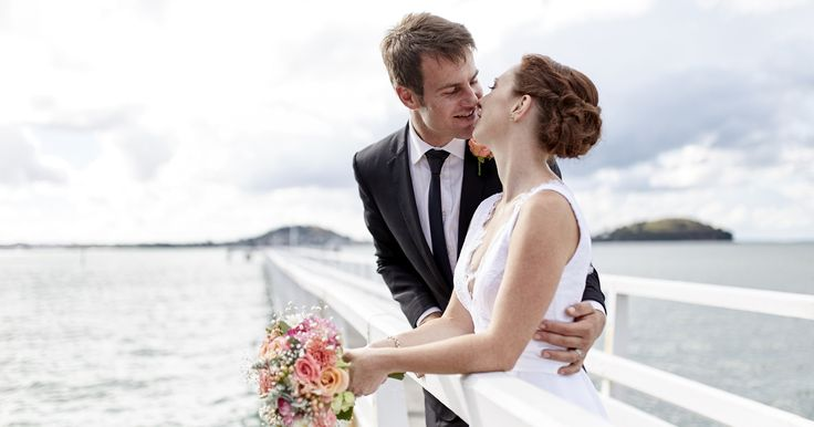 Bride and groom on the jetty in Mission Bay, Auckland City, New Zealand. Captured by Adam Popovic Photography. Auckland wedding photographer.