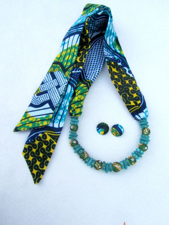 Mooie kleurencombinatie van blauwe en groene sjaal ketting gemaakt van Afrikaanse wax stof en gerecycleerd glaskralen. De lengte is verstelbaar dankzij haar sluiting type (knoop), zonder metalen delen opgenomen. De stijl van deze ketting is variabel en kan gedragen als een sjaal, choker of zelfs als een lange ketting. Het is een echt leuk stuk van juwelen en met uw Aanraking en fantasie kunt u genieten van het dragen van deze ketting op verschillende manieren.  Lengte van deze ketting van…
