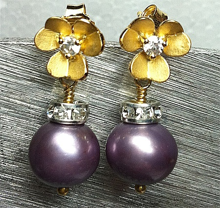 Purple very soft colour, freshwaterbeads 11 mm. On top of here, a cirkel with cz stones. Flower earstud in goldplatted sterlingsilver 925s matt finish. In the middle of the flower one cz stone.  Flower 1 cm.