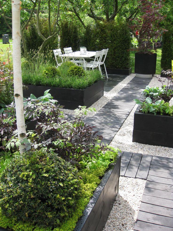 Tydliga linjer, upphöjda växtbäddar, trägångar, sittplats i halvskugga. Trädgård och design för alla: maj 2011