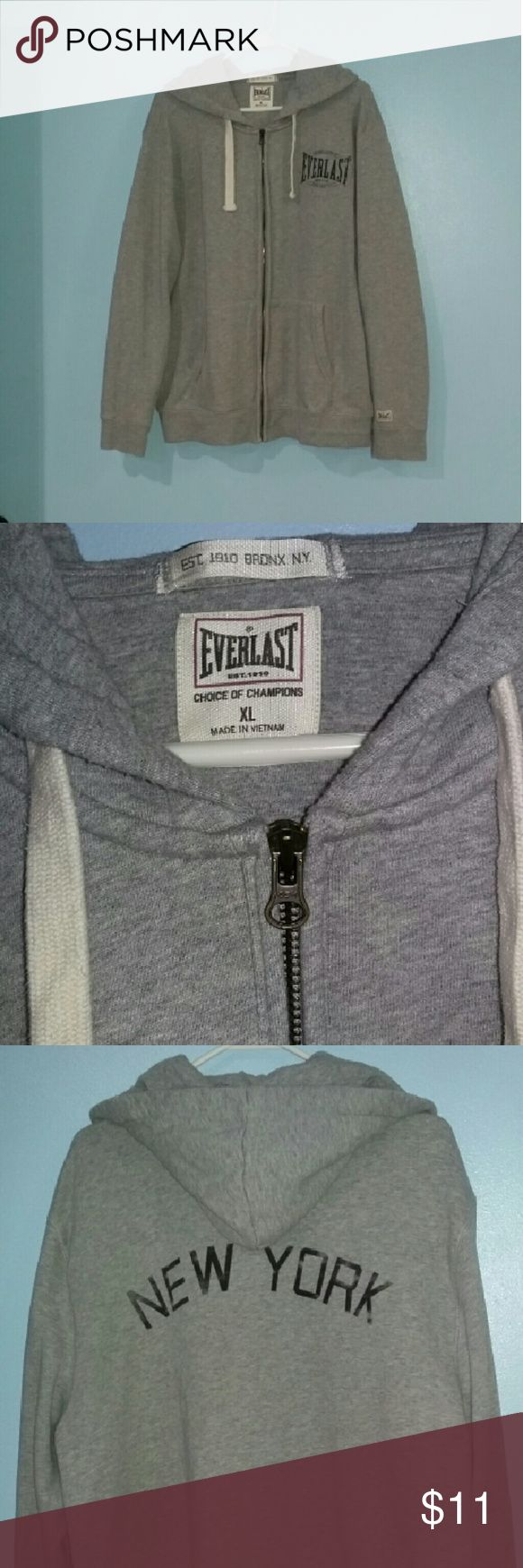 Men's Everlast Hoodie Men's Everlast Choice of Champions Est.1910 grey hooded sweater with circular Boxing Equipment Everlast slightly faded logo on the upper left side.  ✔Has drawstrings through the hood.  ✔Functional zipper!  ✔NEW YORK printed in large letters on the back.  ✔Small Everlast logo patch on the sleeve.  ✔Great condition! Gently used. NO stains, snags, or rips. ✔Size XL Brand is Everlast. Listed as Nike for exposure. Offers are welcome!! Nike Sweaters Zip Up
