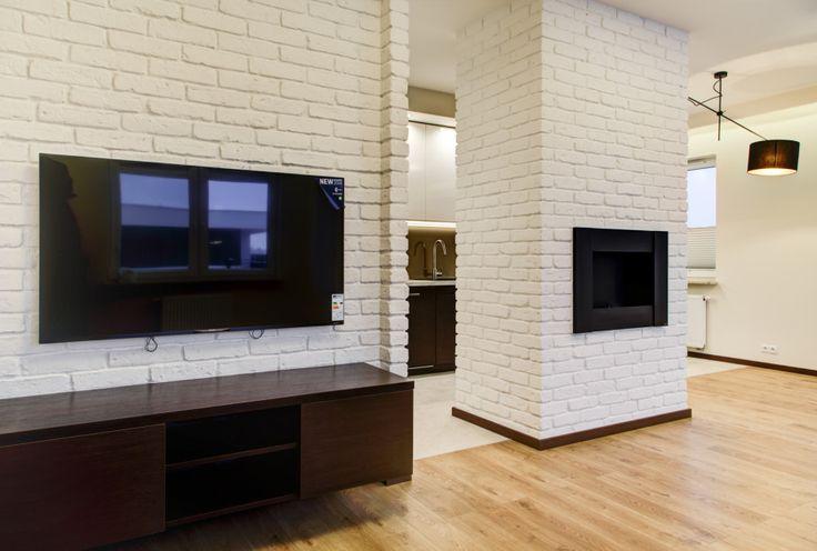 Ceglana ściana w kolorze białym w aranżacji salonu. Ściana z cegieł stanowi idealne tło dla kominka oraz tv.