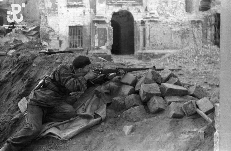 Insurgent in a trench on ul. Długa in Stare Miasto. He is firing a Mauser rifle at German  Panzergrenadiere in the Katedrze Wojska Polskiego (Polish Army Catherdral).