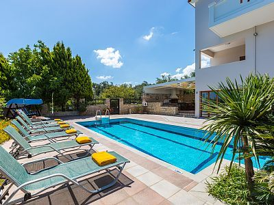 Rethymno villa rental - The pool terrace is equipped with sun beds and umbrellas.