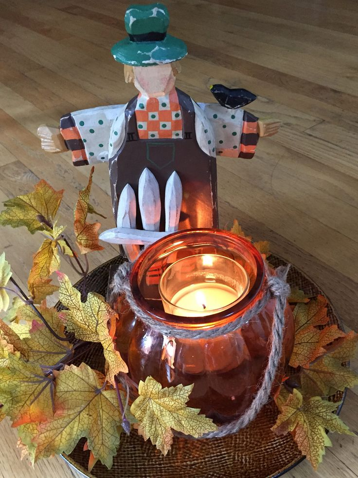Autumn arrangement with pumpkin candle holder with leaves and scarecrow