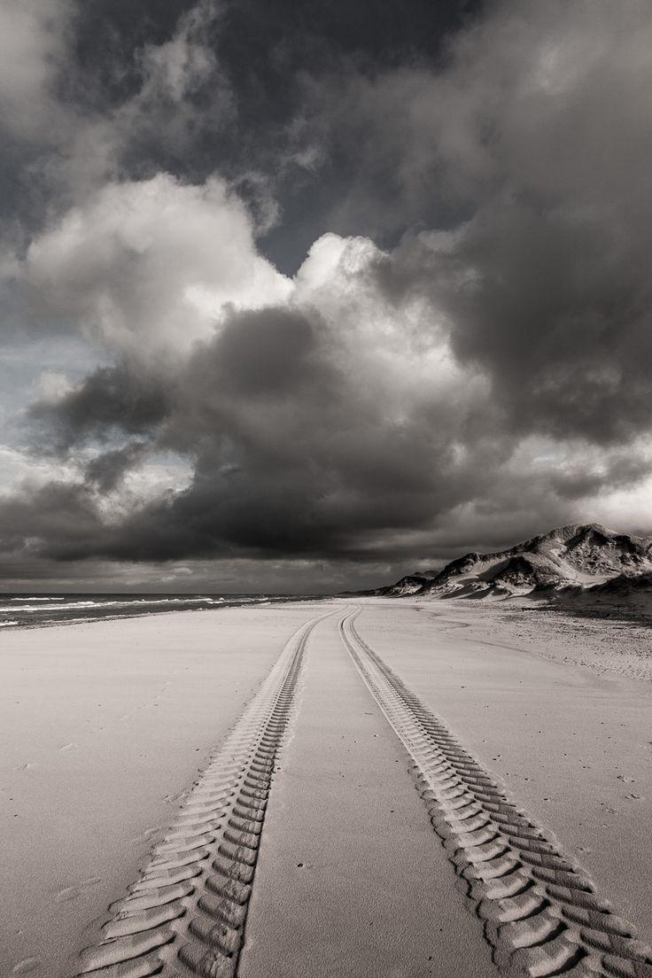 Fotografi af den dramatiske vestkyst ved Skagen Klitplantage. De lyse og mørke skyer blandes på himlen og danner deres eget univers.
