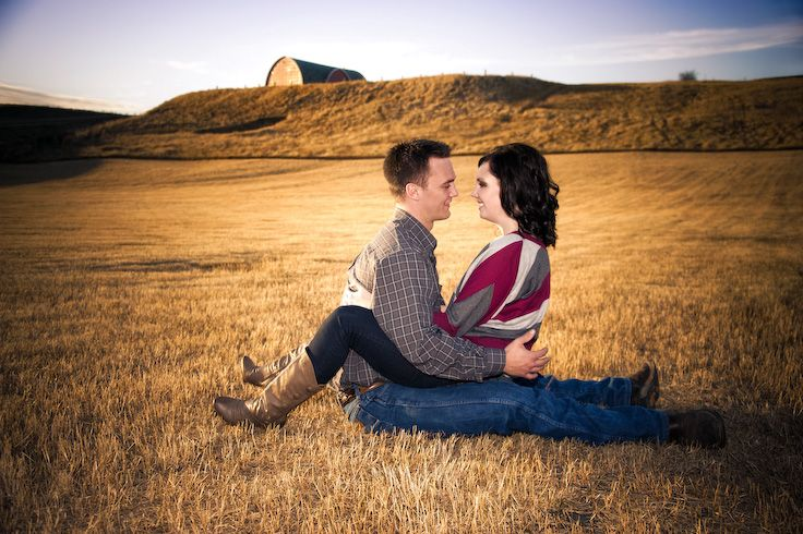 Regina, Saskatchewan Engagement Photography by Pure Photography & Design. Beautiful couple sitting in a field on a farm in the sunset gazing at each other.  www.purephotographyanddesign.com #reginaengagementphotography, #reginaengagementphotographer, #engagementphotographyideas, #reginaweddingphotographer, #reginaweddingphotography, #engagementphotography, #engagementpictures