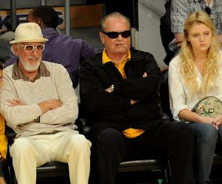 Who Sits Next To Jack Nicholson At Lakers Games?  Music mogul Lou Adler is the person who sits next to Jack Nicholson at Los Angeles Lakers basketball games. Scroll down to see our 10 favorite Jack Nicholson Lakers gifs! There's no celebrity fan out there more closely associated with any team than Jack is with the Lakers. He's had courtside seats for over four decades!  NBA basketball wouldn't be the same without The Joker! The following pic shows Jack and Lou Adler. Nicholson doesn't look…