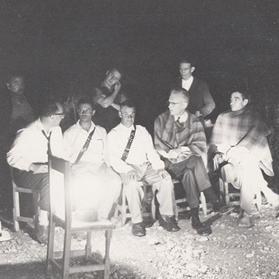 Hector Abad Gomez (left to right the third sitting) and Dr. Richard Saunders (left to right, the sixth sitting) with some men in the community of Versailles, Medellin, 1961