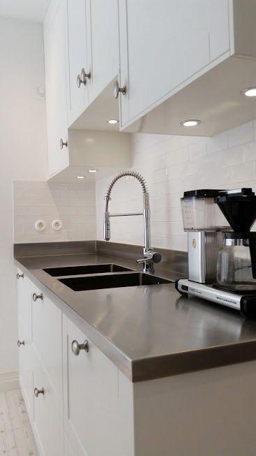 Rostfri diskbänk med dubbla vaskar och 10 cm hög uppvikt kant i bakkant och vänster gaveln.