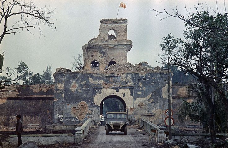 The flag of South Vietnam flies atop a tower of the main fortified structure in the old citadel as a jeep crosses a bridge over a moat in Hue during the Tet Offensive in February of 1968.