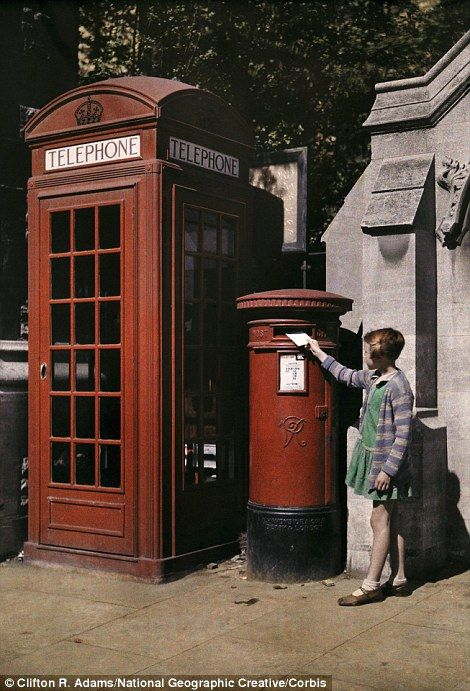 1929, Oxford: A girl places an envelope in a postbox next to a telephone booth...