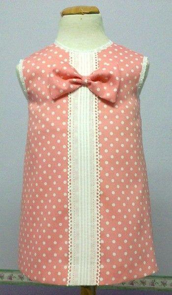 Vestido de bebe niña en pique de canutillo rosa con topitos blancos combinado con entredós y punta bordada con moña a juego.