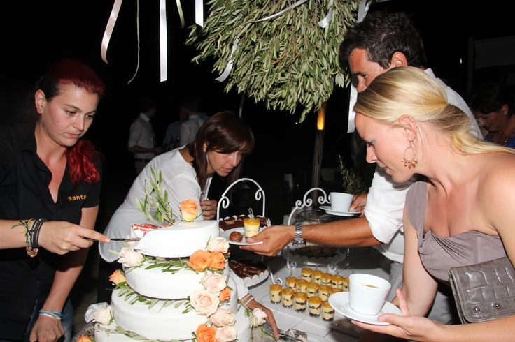 Guests choosing sweets from Mathiassos Bakery from an exquisitely designed sweets table on the beach.#naxosweddings #islandeventsstyles