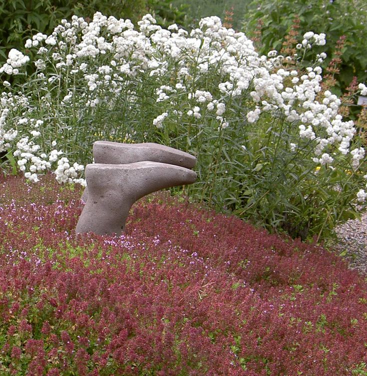 A pair of concrete wellingtons diving into a bed of flowers, it looks playful and fun.