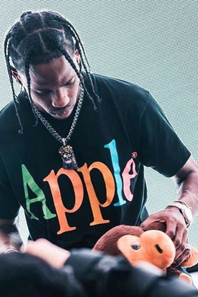 Travis Scott wearing  Vintage 1990s Apple Computers Rainbow T-Shirt, Bape Gold Members 15th Anniversary Baby Milo Plush Toy