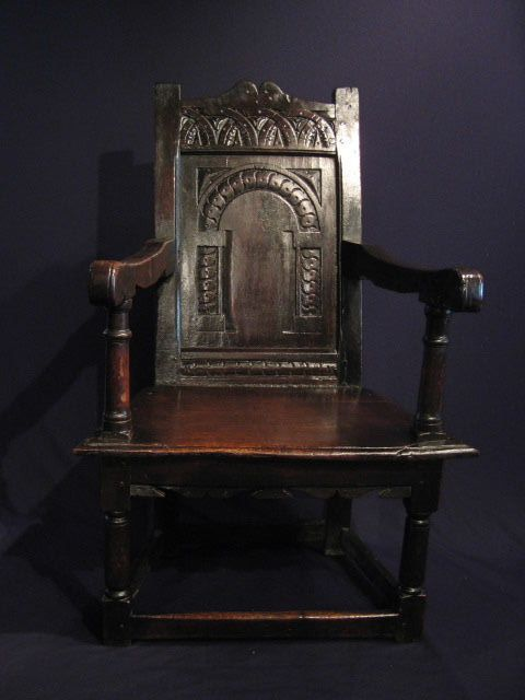 "A FINE EARLY 17TH CENTURY WEST COUNTRY OAK WAINSCOT ARMCHAIR. CIRCA 1630.    THE SHAPED TOP RAIL WITH LUNETTE CARVING ABOVE AN ARCHADED CARVED PANELLED BACK WITH LEAF, BERRY AND INTERLOCKING ""S"" SCROLL DECORATION. WITH A TYPICAL WEST COUNTRY TAPERED SEAT. STANDING ON TURNED LEGS UNITED BY STRETCHERS. FINE COLOUR AND PATINATION. POSSIBLY SALISBURY.  41"" HIGH X 27"" WIDE X 21"" DEEP."