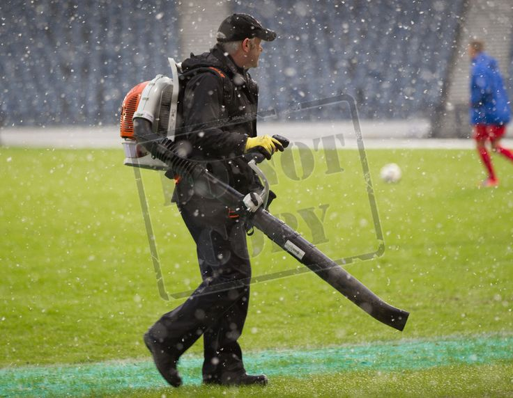Snow being blown off the pitch before the SPFL League Two game between Queen's Park and Montrose