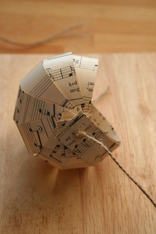 Kerstbal van stroken papier, bijv van een muziekblad
