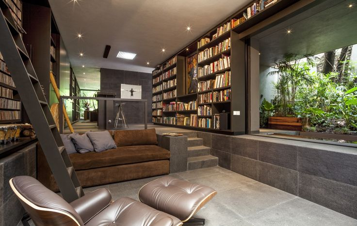 Sunken living room surrounded by bookshelves with an open view of the garden Mexico City Mexico [20001269]