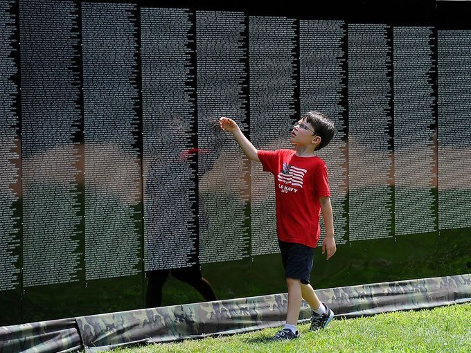 James Doherty looks for a name on a half-size replica of the Vietnam Veterans Memorial on July 4 at Hastings on the Hudson, N.Y. The replica of the Washington, D.C., memorial has been on tour across the country for 30 years.