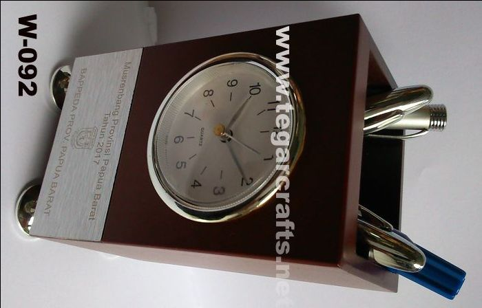 W044: An analog desk clock plus pen holder made from wood with metal plate for branding logo and provided with four legs. Size 7.6x 7.5 x 12.8cm It's an ideal choice to use as a goverments souvenir, institution, or national working meeting -Rapat Kerja Nasional- (Rakornas), or National Working Comitee. As shown a wooden desk clock for Musrenbang -Musyawarah Perencanaan Pembangunan (Development Planning) held by Pemerintah Provinsi Papua Barat, Indonesia.