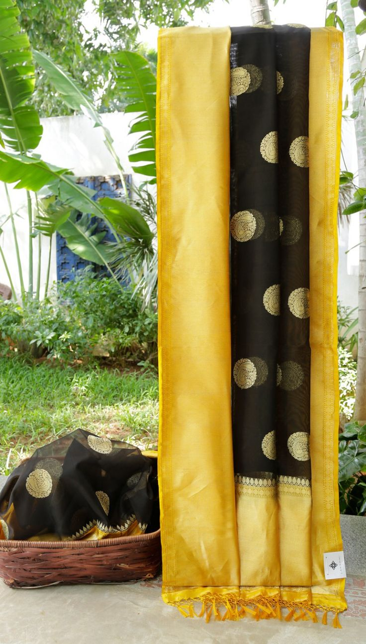 This black coloured Benares kora has large, round gold zari bhuttas. The border is in canary yellow, medallion yellow and gold zari while the pallu is in canary yellow and gold zari giving it a con…