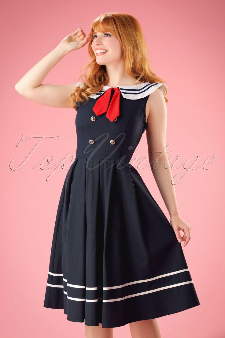 Ahoy captain! Snel aan boord en 'sail away' in deze50s Aquarius Sailor Swing Dress! Pas maar op dat je geen boten laat kapseizen in deze prachtige swing jurk in typische 50s sailor stijl! Zwierige swing rok, ronde halslijn met speelse nautische omslag kraag en een schattig rood strikdetail, too cute! Nog niet sailor 'proof' genoeg voor je?... nou, ze wordt ook nog eens opgeleukt door vier antiek goudkleurige sierknopen voorzien van ankertjes en is aan de onderkant af...