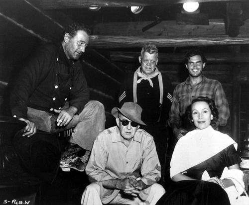 John Wayne, director John Ford, Jack Pennick and Jeffrey Hunter pose with visitor Dolores Del Rio on the set ofThe Searchers