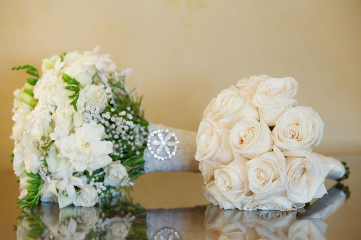 """The Bachelorette"" star Ashley Hebert carried a bouquet composed of a variety of white florals wrapped in lace, while her bridesmaids carried single variety nosegays. #whitebouquet Photography: Bob & Dawn Davis Photography. Read More: https://www.insideweddings.com/weddings/ashley-hebert-and-jp-rosenbaum/438/"
