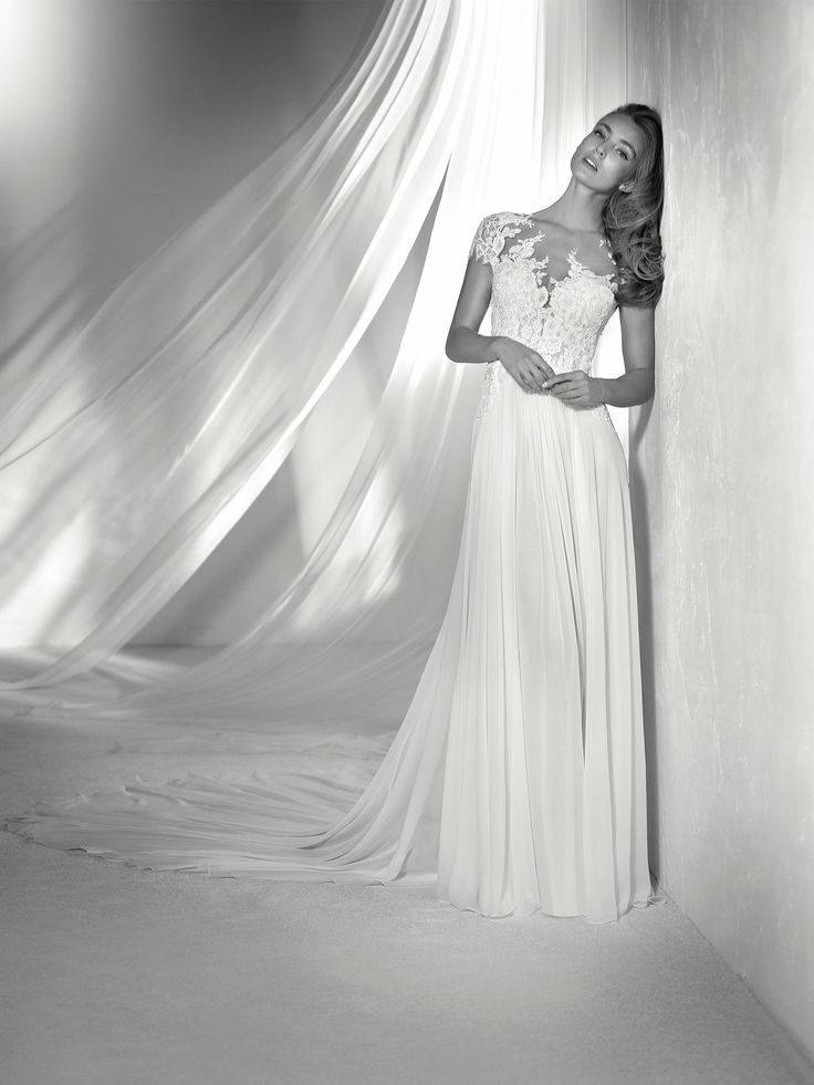REGINA: Lovely wedding dress with a chiffon and tulle skirt featuring beaded appliqués and a tattoo neckline with elegant floral details. Pronovias 2018 Collection
