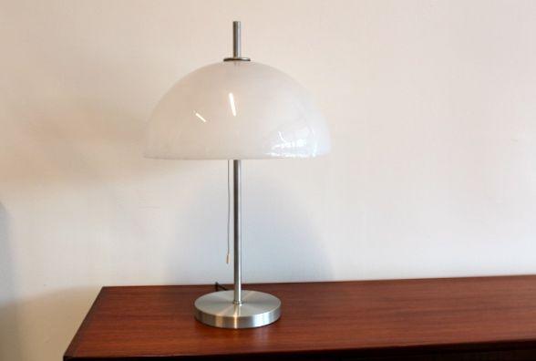 Raak 185 Mushroom Tafellamp Karakteristieke Mushroom Tafellamp ontworpen voor Raak Amsterdam in de jaren '70. De lamp is groot van formaat en een schitterend object in de ruimte met een aangename lichtopbrengst. De zeer stabiele voet is gemaakt van metaal. De kap is gemaakt van kunststof en in perfecte staat. Deze constructie maakt de lamp zeer stabiel.  Hoogte: 50 Doorsnede: 38 Conditie: uitstekend Prijs: € 285,-