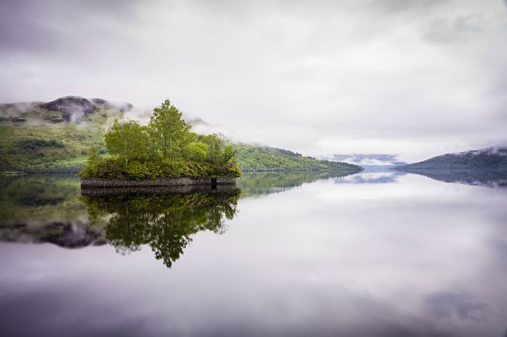 Scenic view of small wooded island on loch, Loch Katrine, The Trossachs.