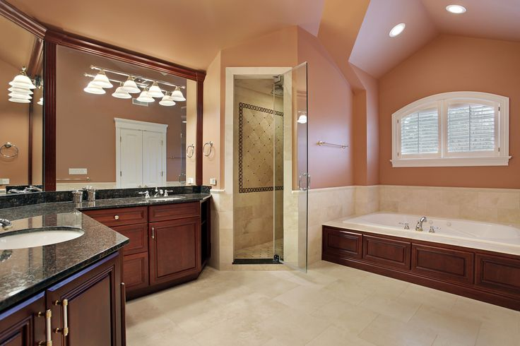 Spacious bathroom in a new home.  I would prefer white walls over salmon colored walls, but the custom wood work looks great.