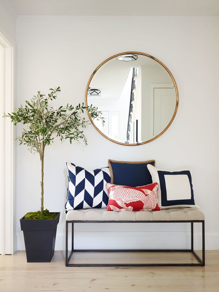 Home Entryway With Large Circular Wall Mirror And Metal Framed Bench Seating  With Accent Pillows