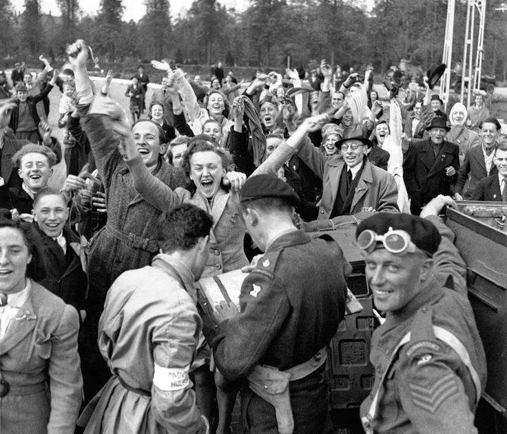 Jubilant Dutch civilians gather to welcome their liberators. Units of the 1st Canadian Army entered Utrecht on 7 May 1945 coming through Biltstraat in order to enter the old city center as residents lined the streets in masses to celebrate their arrival. The soldiers pictured are actually British, from the 49th (West Riding) Infantry Division, who were often attached to the 1st Canadian Army (in April as part of 1st Corps). Utrecht, Utrecht Province, Netherlands. 7 May 1945. Image taken by…