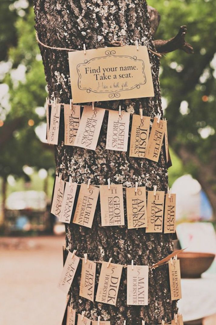 Wrap twine around a tree trunk and clip escort cards to it for a rustic-chic look!