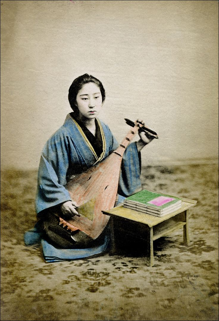 The biwa (琵琶) is a short-necked fretted lute. With four strings and four frets, I believe this is a Satsuma-biwa (薩摩琵琶). Handcolored albumen print. Japan, ca. 1900. Unidentified photographer.