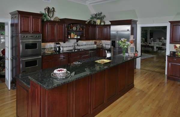 Cherry Cabinets With Crown Molding And Dark Granite