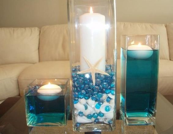 """Centerpieces...I like the idea, but I'd do clear water and shells in the bottom...I like the candle in sand, and the starfish...it ties back to the star fish """"place cards"""", the blue ties in our cute nautical napkins and one branch of flowers ties in the food displays.  Marvelous!"""