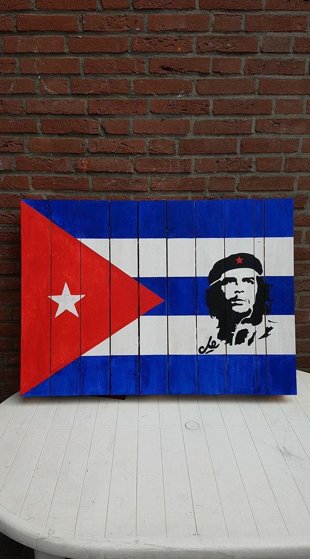 Cubaanse vlag met afbeelding Che Cuevara op een houten pallet geschilderd. Eerst het hout behandelen met gesso, grondverf. Daarna met gewone acrylverf beschilderen. Voor de afbeelding van Che, gebruik een sjabloon, online gekocht. Als laatste aflakken.