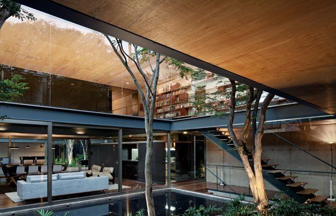 A galeria de circulação do piso superior abre-se para o jardim externo e para a sala de estar Una arquitetos