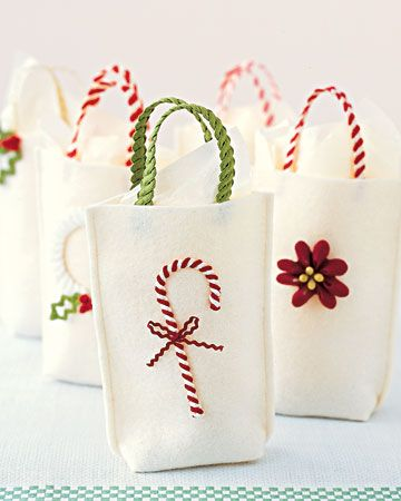Gift Bags with a Twist... make simple felt sacks (sew side seams, fold bottom corners toward the center, tack with thread). embellish with rickrack handles and a bright ornament. the sturdy grips are nothing more than two lengths of intertwined trim.