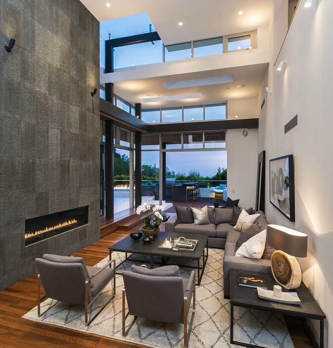 A modern design with high ceilings and open spaces give this living room a very spacious feel. A long fireplace sits in the wall to the side, and large windows give us a great view of the outdoor patio and bar. Do you like this modern style? Source: http://www.zillow.com/digs/Home-Stratosphere-boards/Luxury-Living-Rooms/