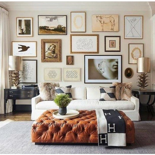 Gorgeous Art Wall With A White Sofa And Large Tufted Ottoman