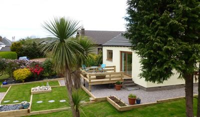 Woodlea - Self Catering Accommodation lsle of Arran, Scotland, the view of the landscaped garden and deck area off the lounge.
